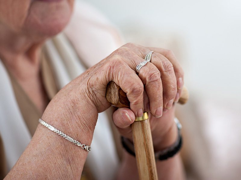 Elderly Woman holding a stick sitting down