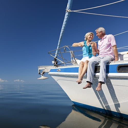 Happy Senior Couple on the Bow of a Sail Boat - Corporate Finance image