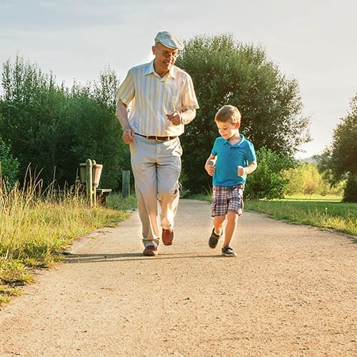 Financial Planning - Man with his grandson running along a path