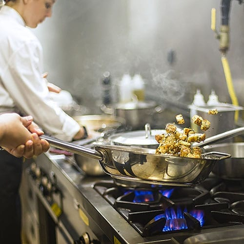 Food and drink image - chef cooking next to gas cooker