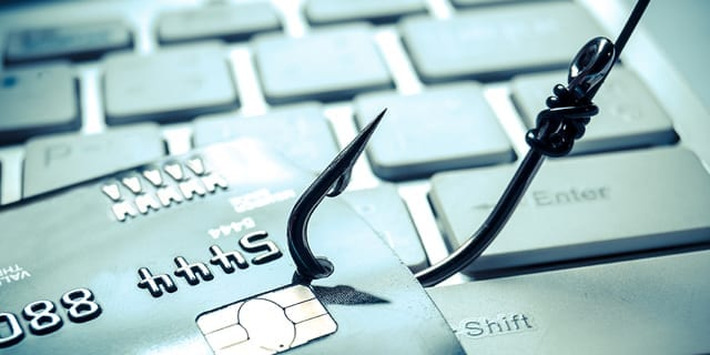 Fishing Hook Through A Credit Card On Front Of A Keyboard