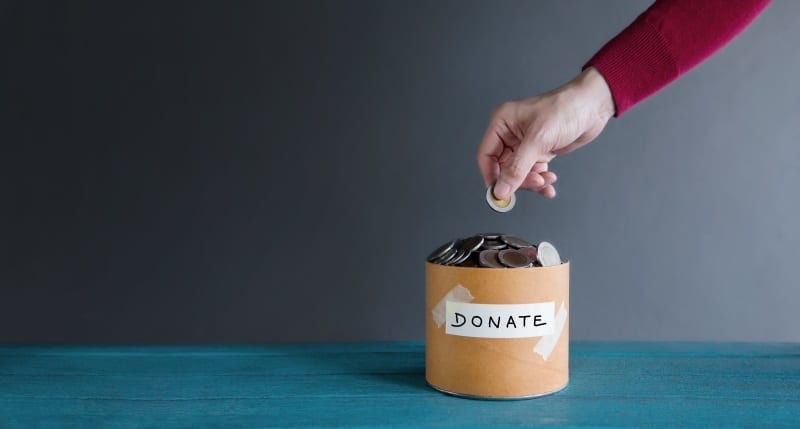 Dropping Coins Into Donation Tin