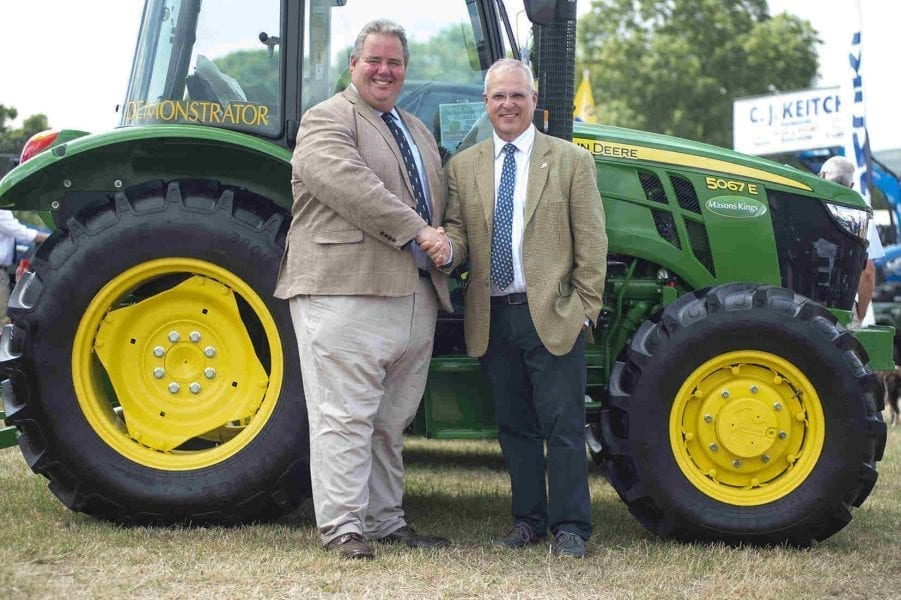 Two Men Shaking Hands In Front Of Tractor