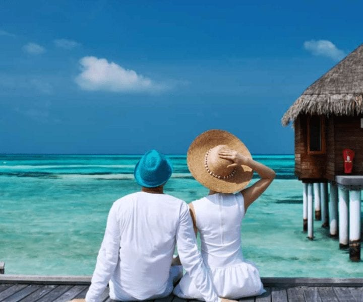 Couple Sitting On Pier In Maldives