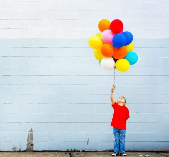Young Boy Holding Bunch Of Balloons