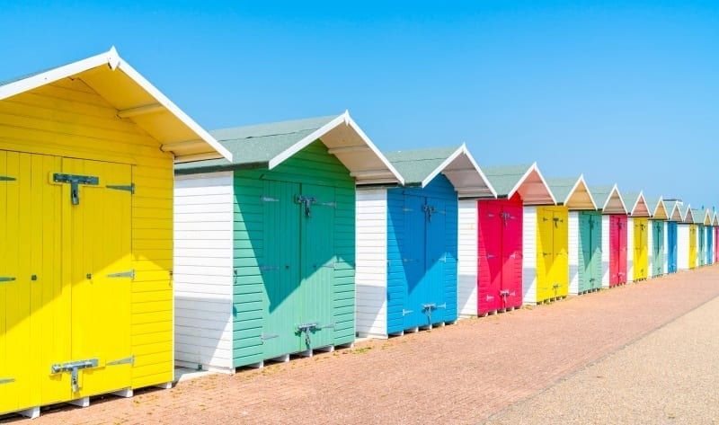 A Row Of Colourful Wooden Beach Huts On The Beach