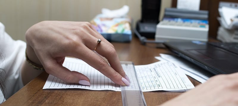 Woman Using Ruler On Paper Form Document